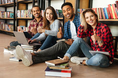 Smiling students sitting in library on floor using laptop Stock Image