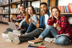Smiling students sitting in library on floor using laptop Royalty Free Stock Photo