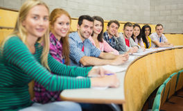 Smiling students sitting in a row at lecture hall Stock Photos