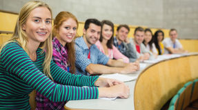 Smiling students sitting in a row at the lecture hall Royalty Free Stock Image