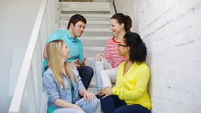 Smiling students sitting on stairs and talking stock video