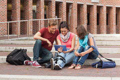 Smiling students sitting on stairs using tablet Royalty Free Stock Photography