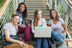 Smiling students sitting on steps with laptop Stock Photography