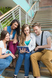 Smiling students sitting on steps with tablet pc Stock Image