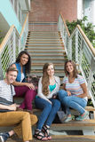 Smiling students sitting on steps Stock Image
