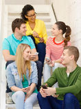 Smiling students with smartphone having discussion Royalty Free Stock Image