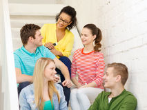 Smiling students with smartphone having discussion Royalty Free Stock Photos