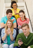 Smiling students with smartphone texting at school Royalty Free Stock Photography
