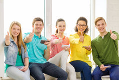 Smiling students with smartphone texting at school Stock Image