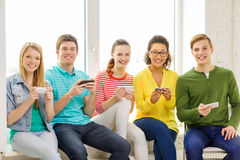 Smiling students with smartphone texting at school Stock Photo