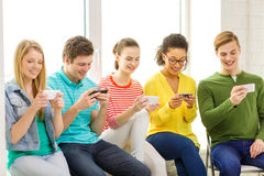 Smiling students with smartphone texting at school Royalty Free Stock Images