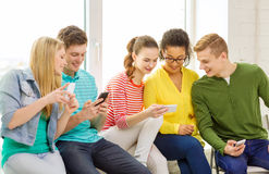 Smiling students with smartphone texting at school Royalty Free Stock Image