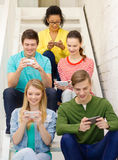 Smiling students with smartphone texting at school Stock Images