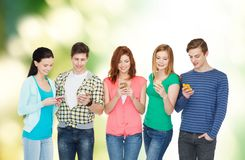 Smiling students with smartphones Stock Photo