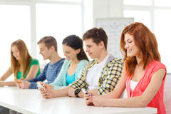 Smiling students with smartphones at school Stock Photography