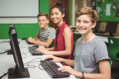 Smiling students studying in computer classroom. At school Stock Photo