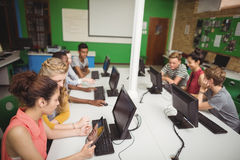 Smiling students studying in computer classroom Royalty Free Stock Photography