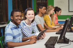 Smiling students studying in computer classroom Stock Photo
