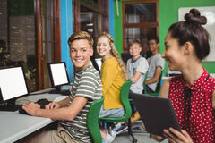 Smiling students studying on digital tablet and computer in classroom Stock Photography