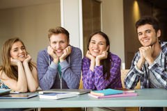 Smiling students studying together and look at camera Stock Images