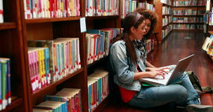 Smiling students studying together sitting on floor in library stock video