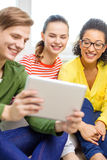 Smiling students with tablet pc computer Royalty Free Stock Image