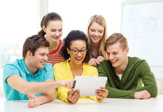 Smiling students with tablet pc computer at school Stock Photos