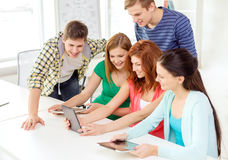 Smiling students with tablet pc at school Royalty Free Stock Photos