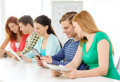 Smiling students with tablet pc at school Stock Photography