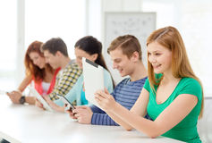 Smiling students with tablet pc at school Royalty Free Stock Image