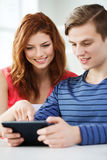 Smiling students with tablet pc at school Royalty Free Stock Images