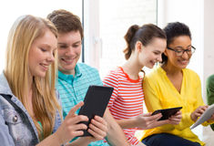 Smiling students with tablet pc at school Royalty Free Stock Photo
