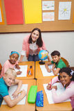 Smiling students and teacher looking at the camera Stock Photography