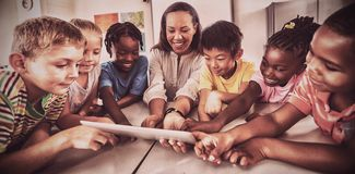 Smiling students and teacher using a tablet computer stock photo