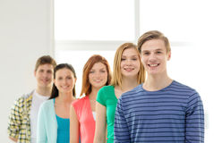 Smiling students with teenage boy in front Royalty Free Stock Images