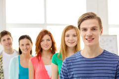 Smiling students with teenage boy in front Royalty Free Stock Photos