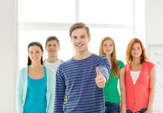 Smiling students with teenage boy in front Stock Photography