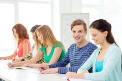 Smiling students with textbooks at school Stock Photos