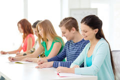 Smiling students with textbooks at school Stock Images