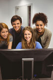 Smiling students using computer together looking at camera Stock Images