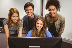 Smiling students using computer together looking at camera Royalty Free Stock Photos