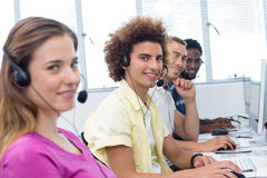 Smiling students using headsets in computer class Royalty Free Stock Photography