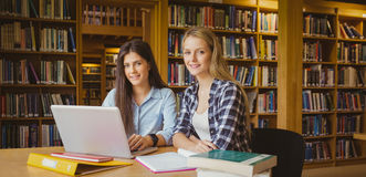 Smiling students using laptop Stock Photo