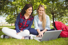 Smiling students using laptop Royalty Free Stock Images