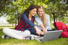 Smiling students using laptop Stock Photos