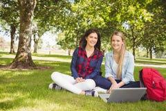 Smiling students using laptop Stock Photo