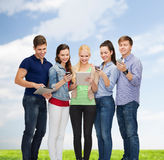 Smiling students using smartphones and tablet pc Stock Photos