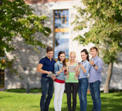 Smiling students using smartphones and tablet pc Royalty Free Stock Image