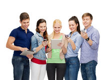 Smiling students using smartphones and tablet pc Stock Images