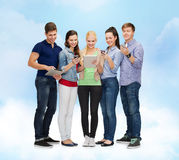 Smiling students using smartphones and tablet pc Royalty Free Stock Photography
